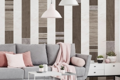 Pink pillows on grey couch in white apartment interior with poster and lamps above table. Real photo